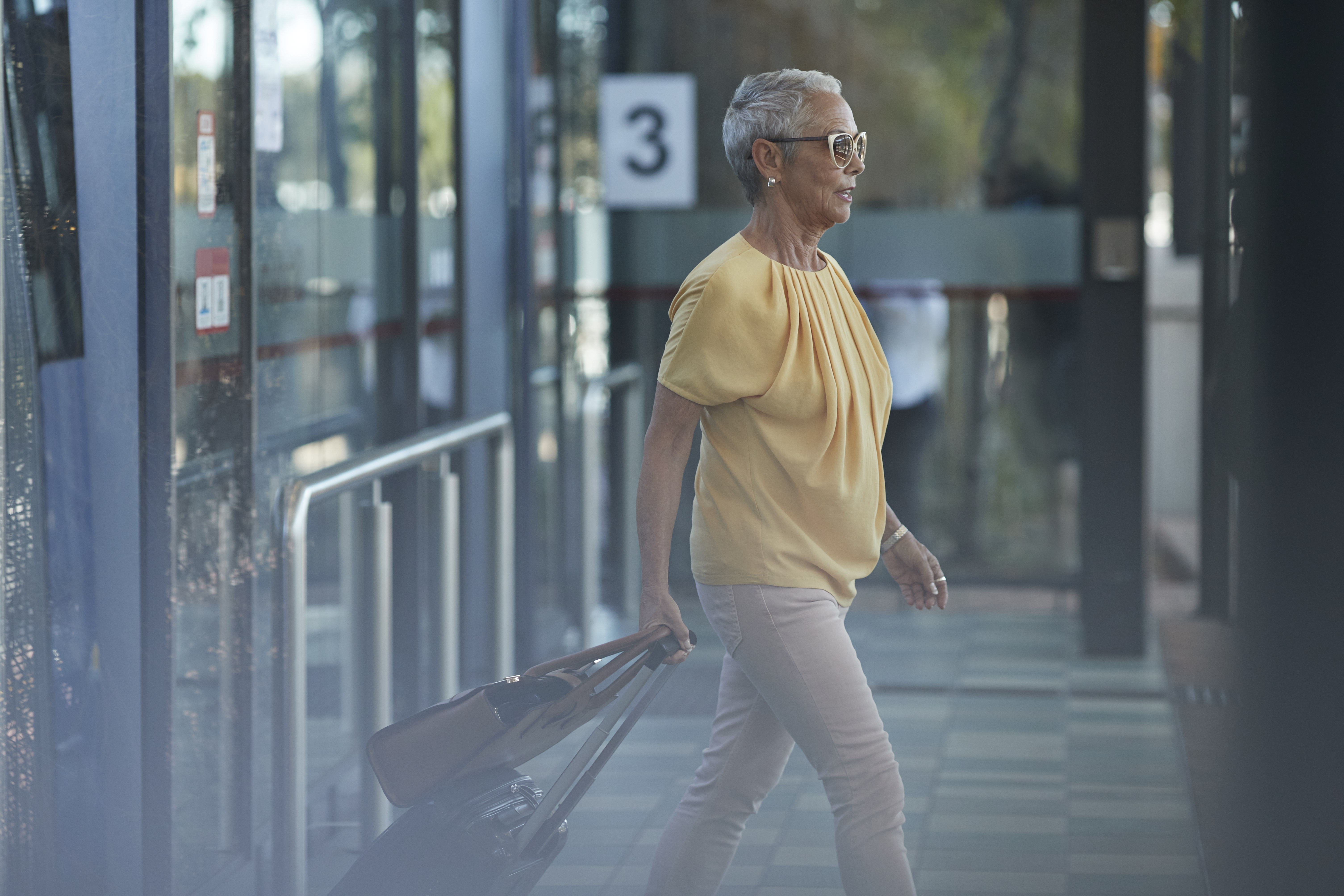 Senior woman walking out of bus, on to public transport platform