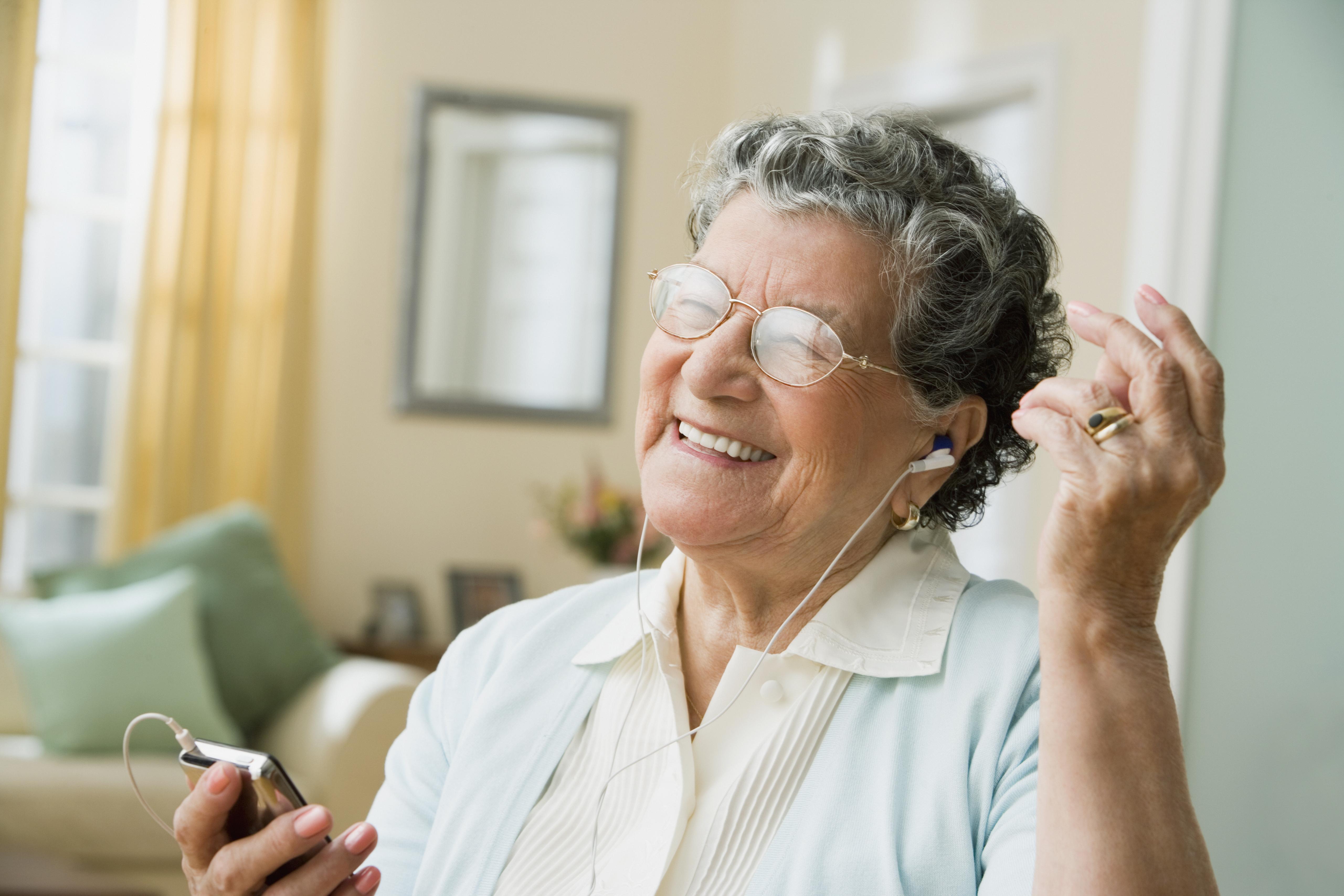 Senior Hispanic woman listening to mp3 player