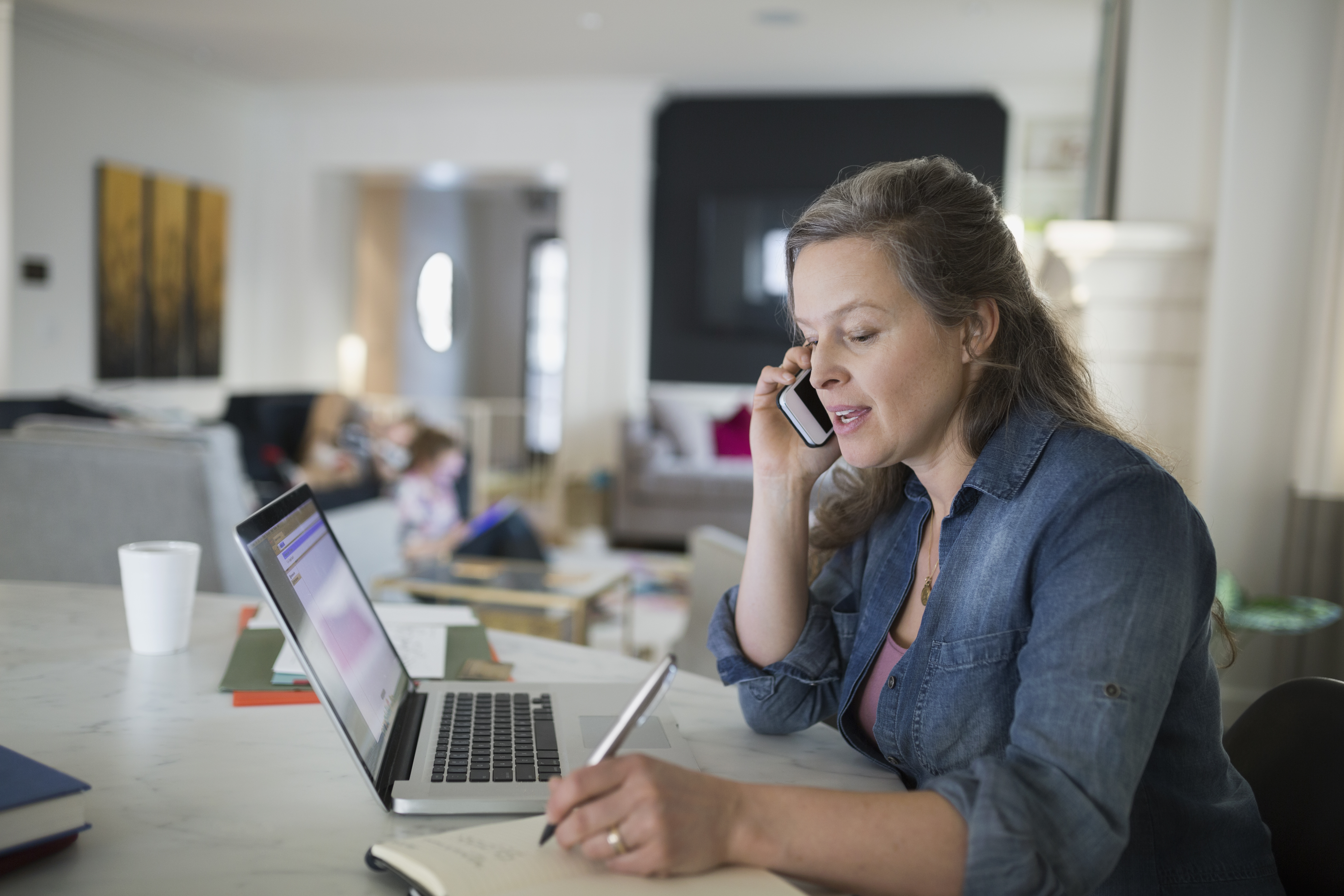 Woman talking on cell phone laptop at table