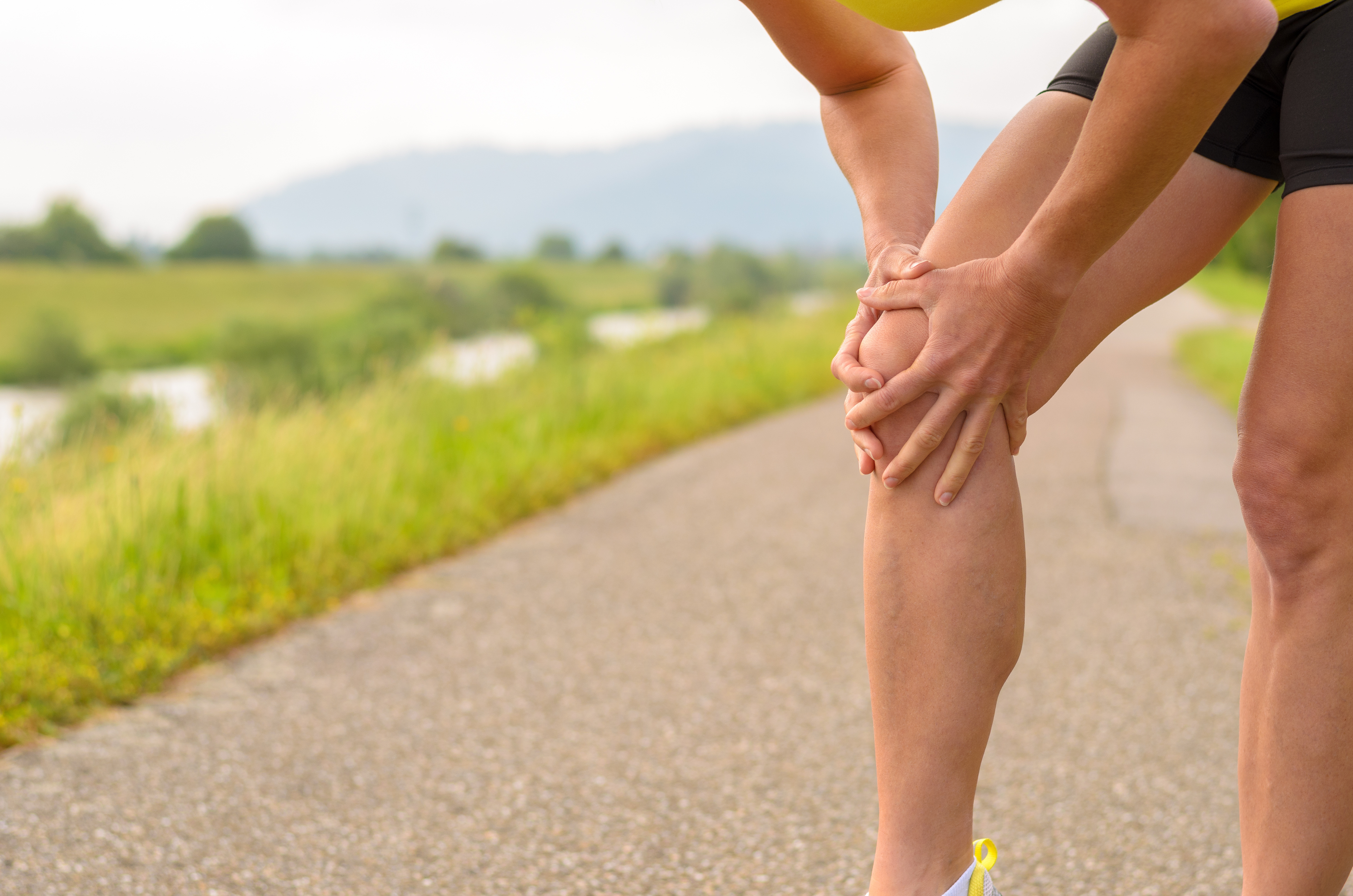Midsection Of Woman Holding Knee During Pain On Footpath