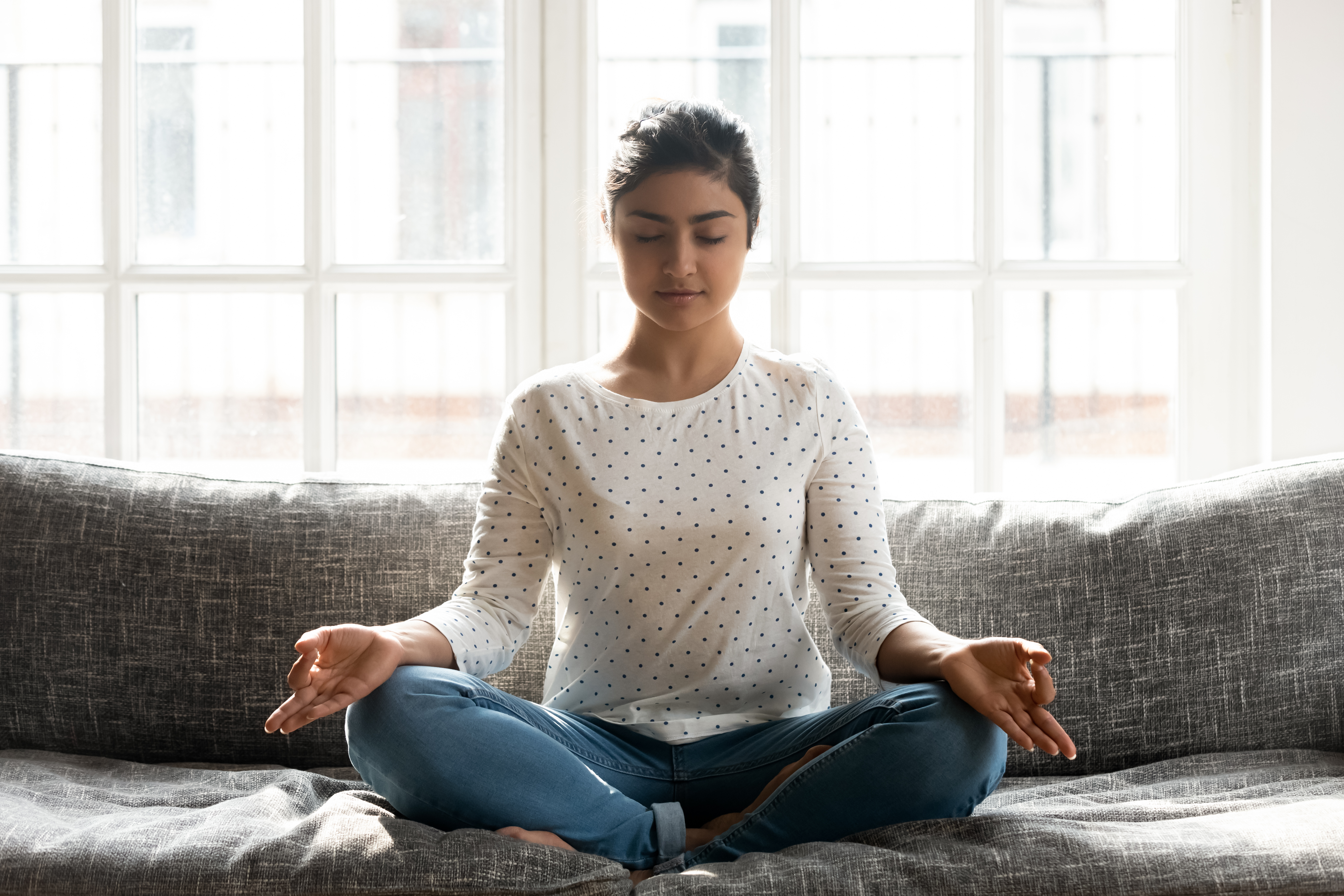 Mindful young indian woman doing breathing yoga exercises alone.