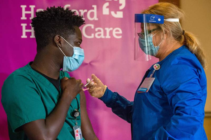 A health care worker receives a COVID-19 vaccine at <br>the Hartford Convention Center.