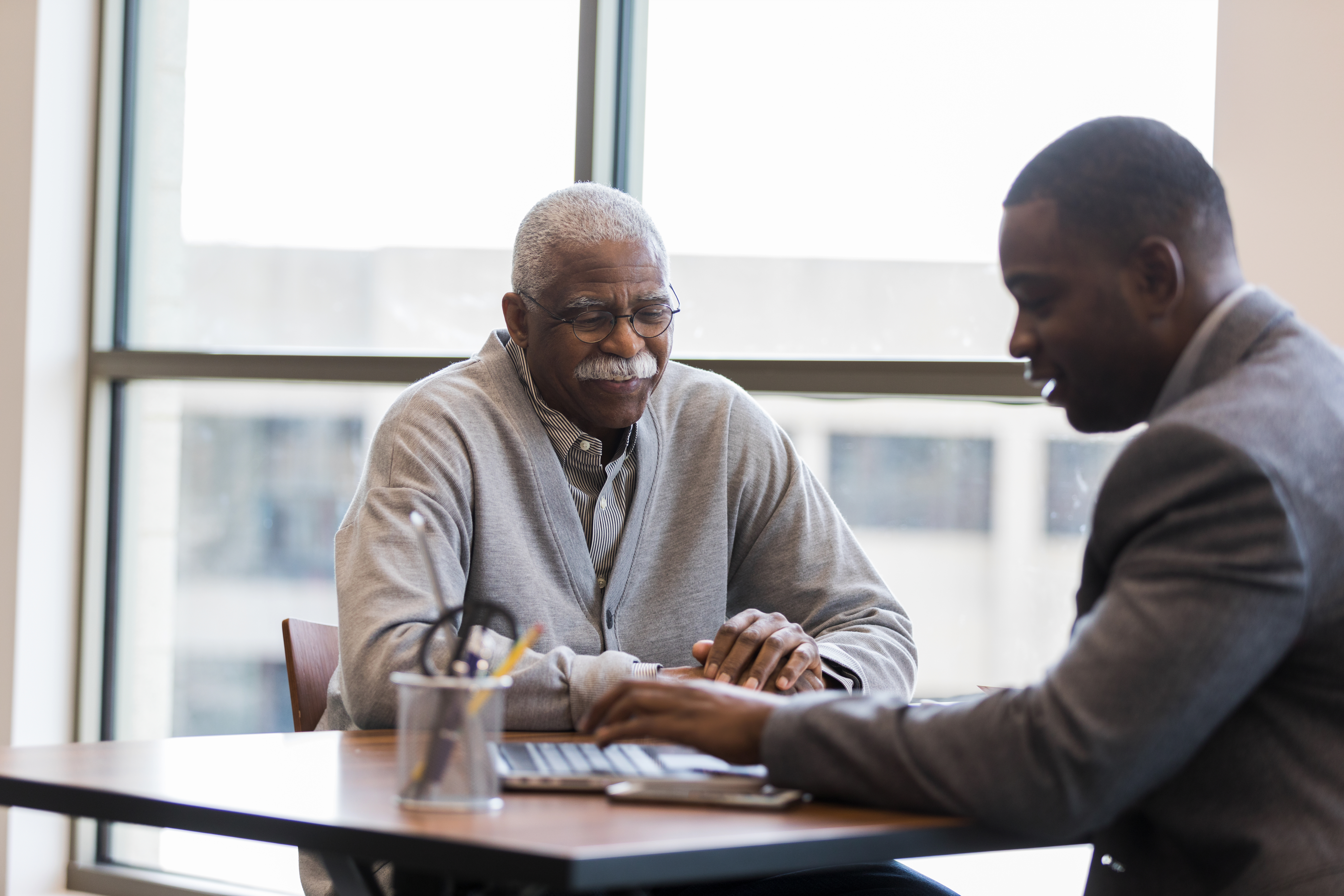 Mid adult loan officer helps senior man find best investment