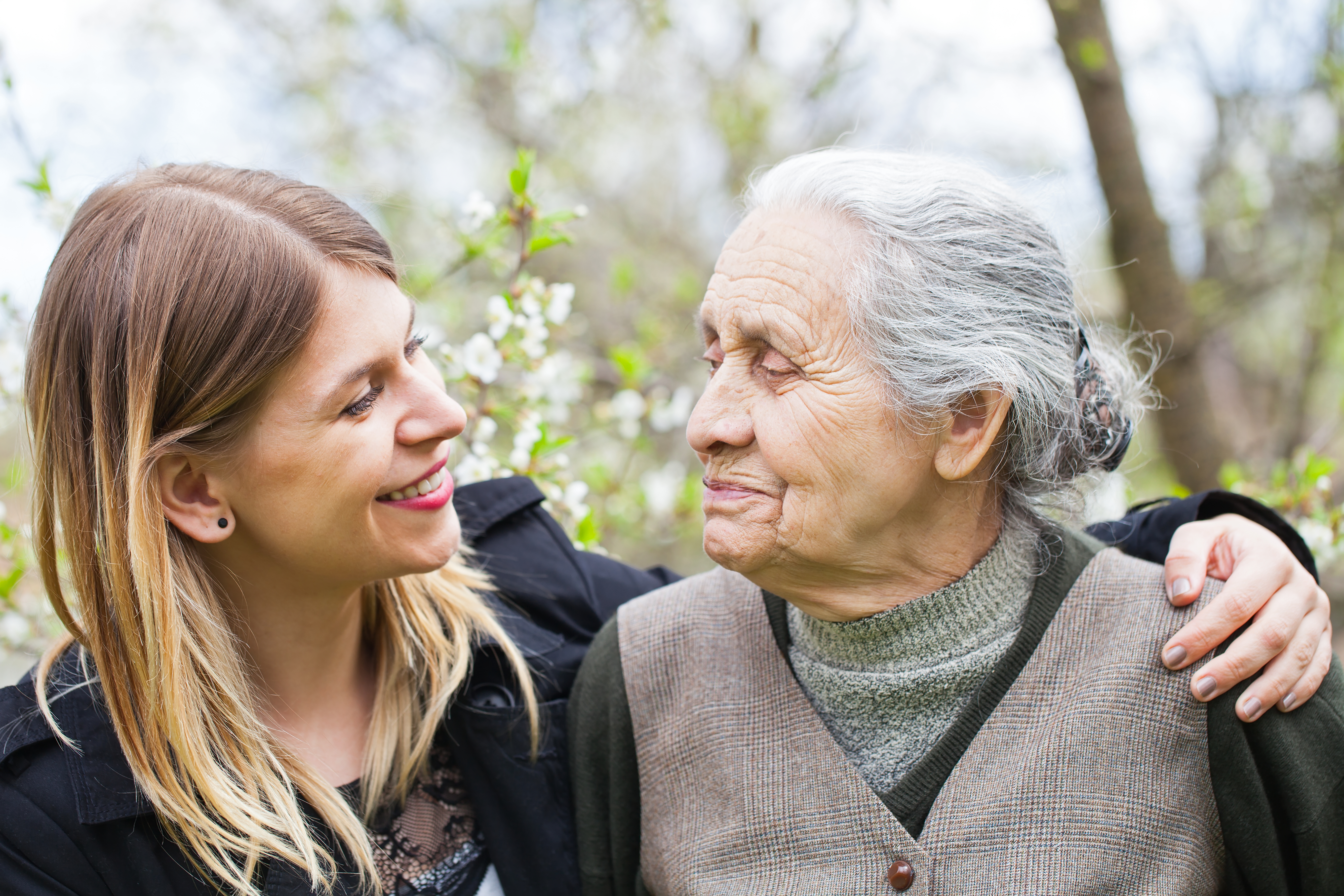 Happy elderly woman with carer outdoor - springtime