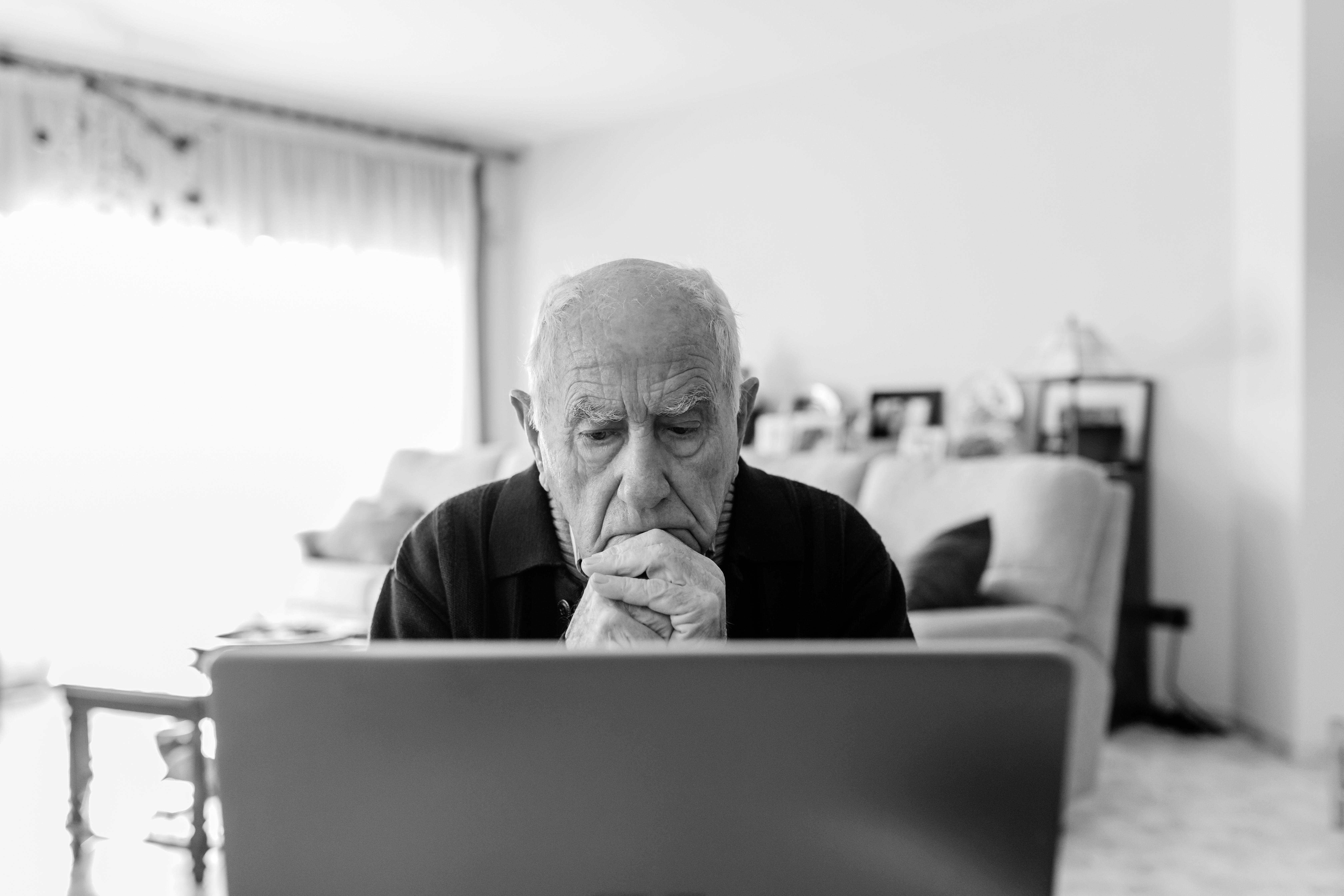 Portrait of senior man using laptop at home