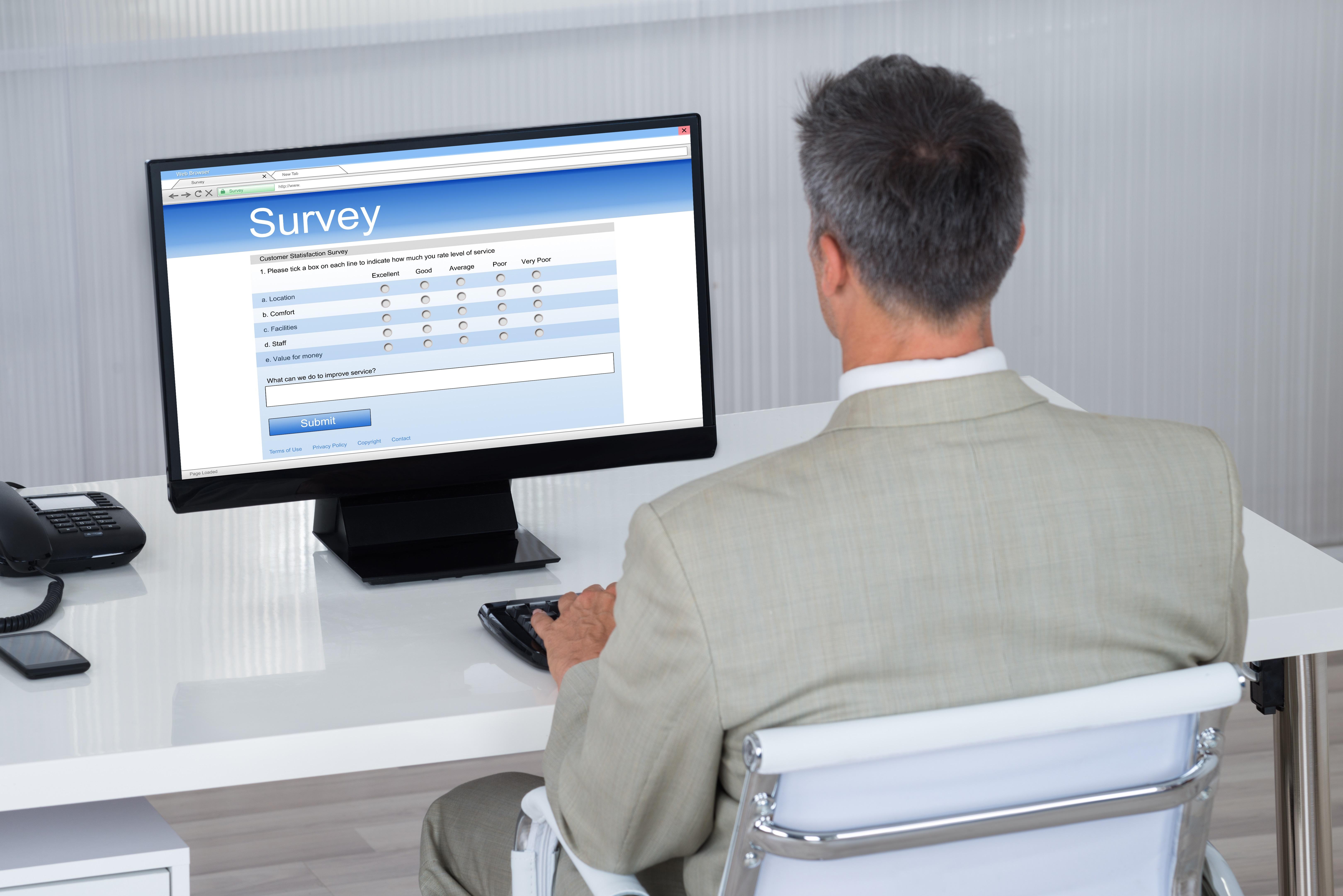 Businessman Filling Survey Form On Computer At Desk