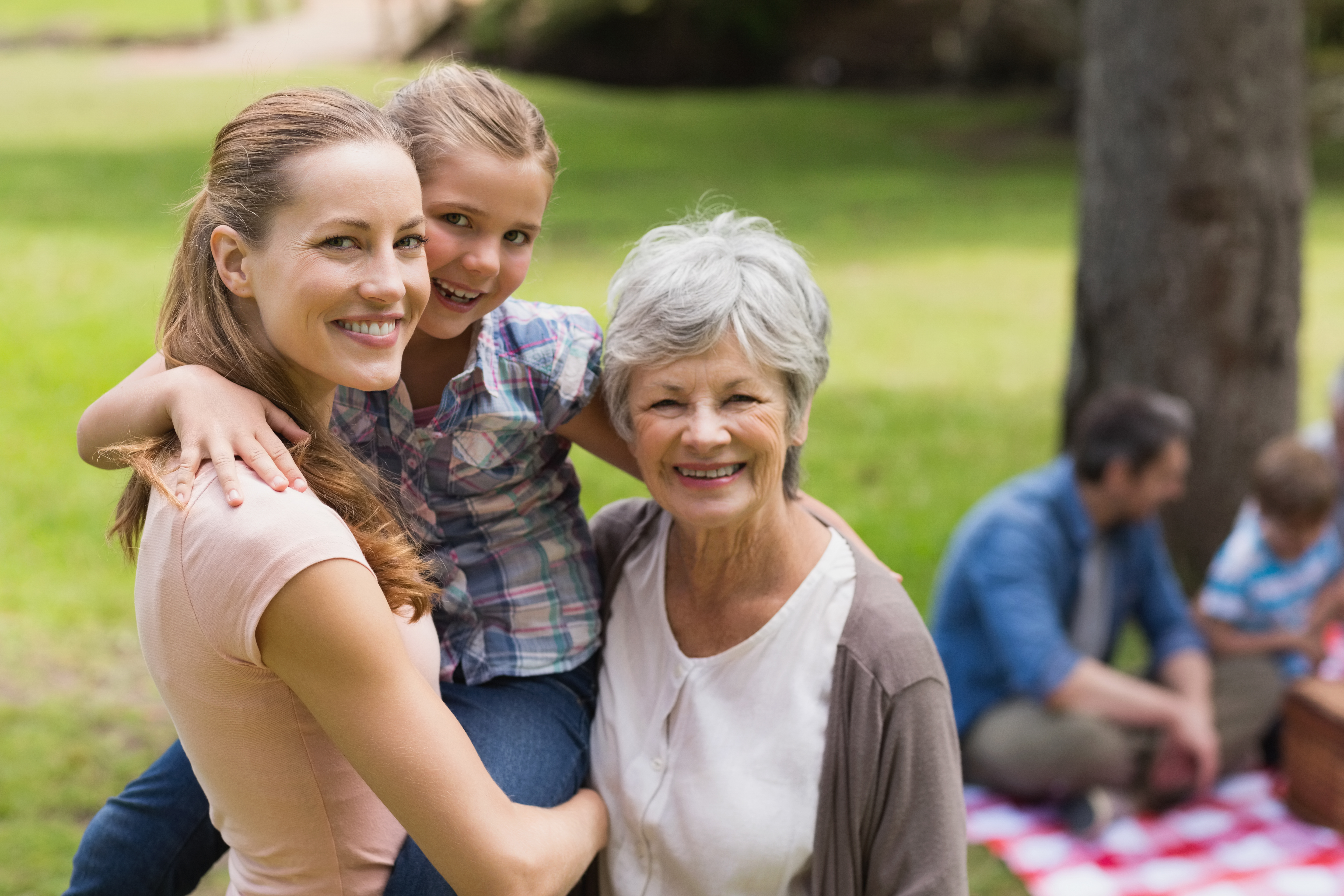 Grandmother mother and daughter with family in background at park