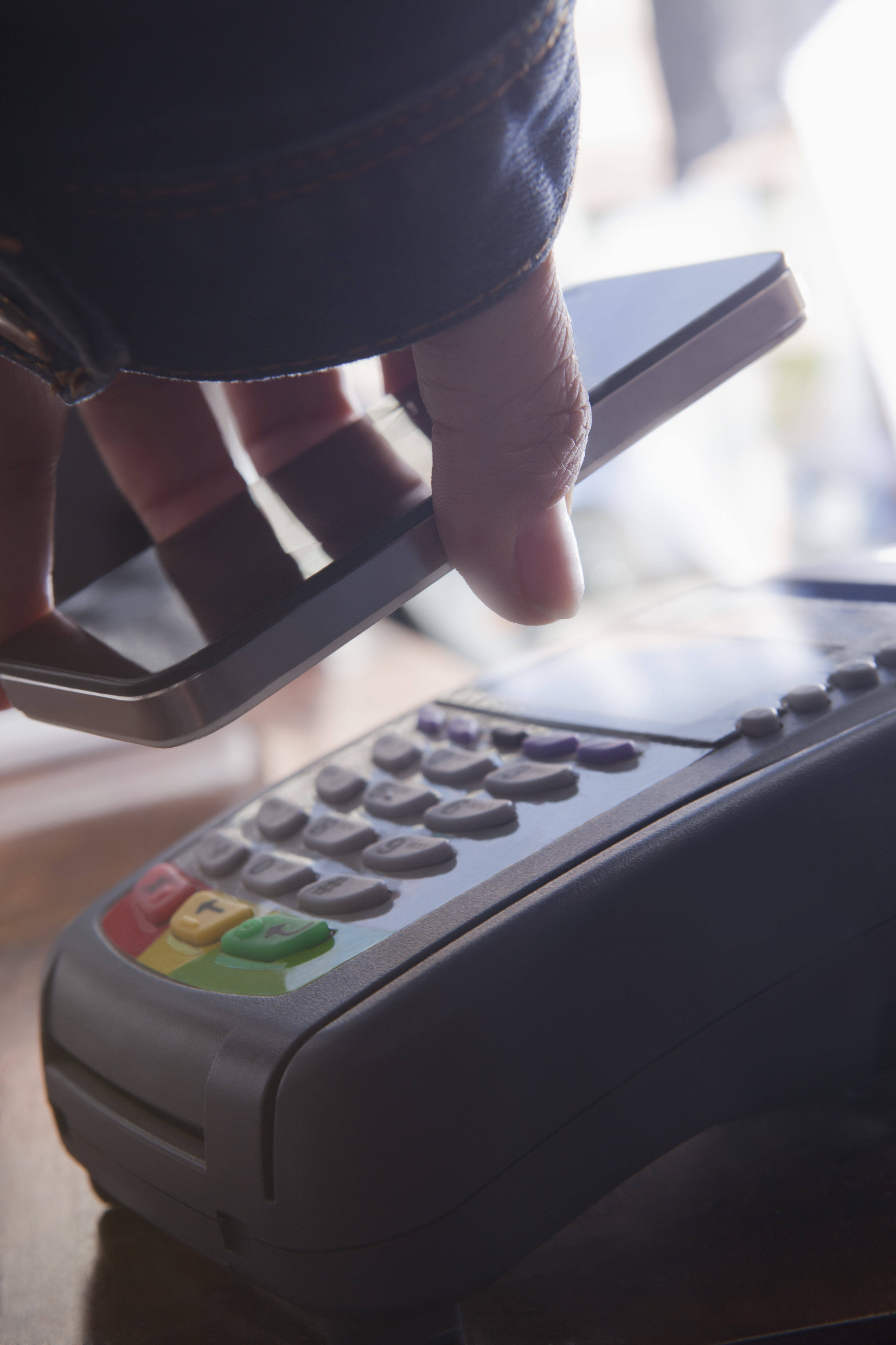 Hispanic woman scanning credit card from cell phone