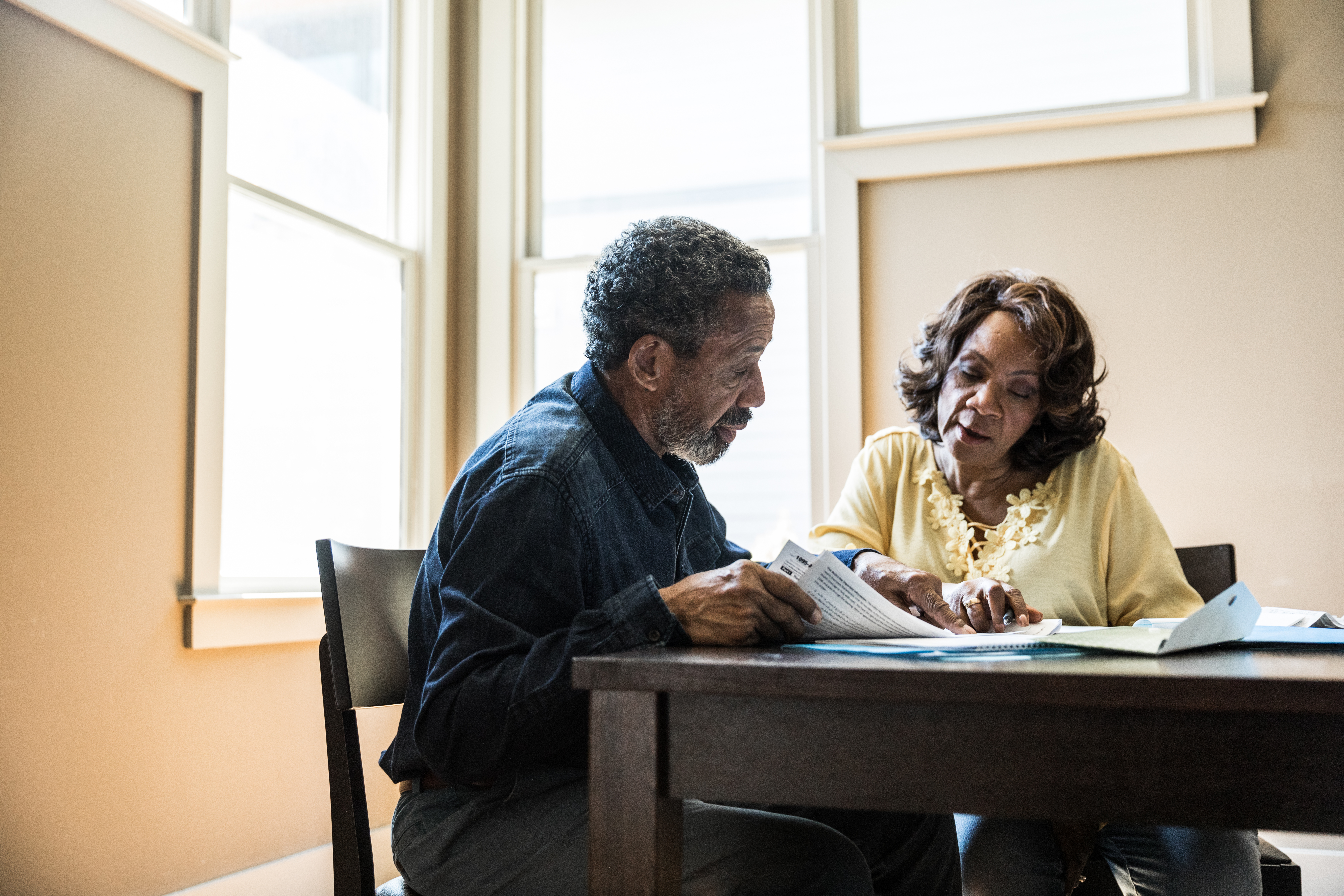 Senior couple paying bills at home