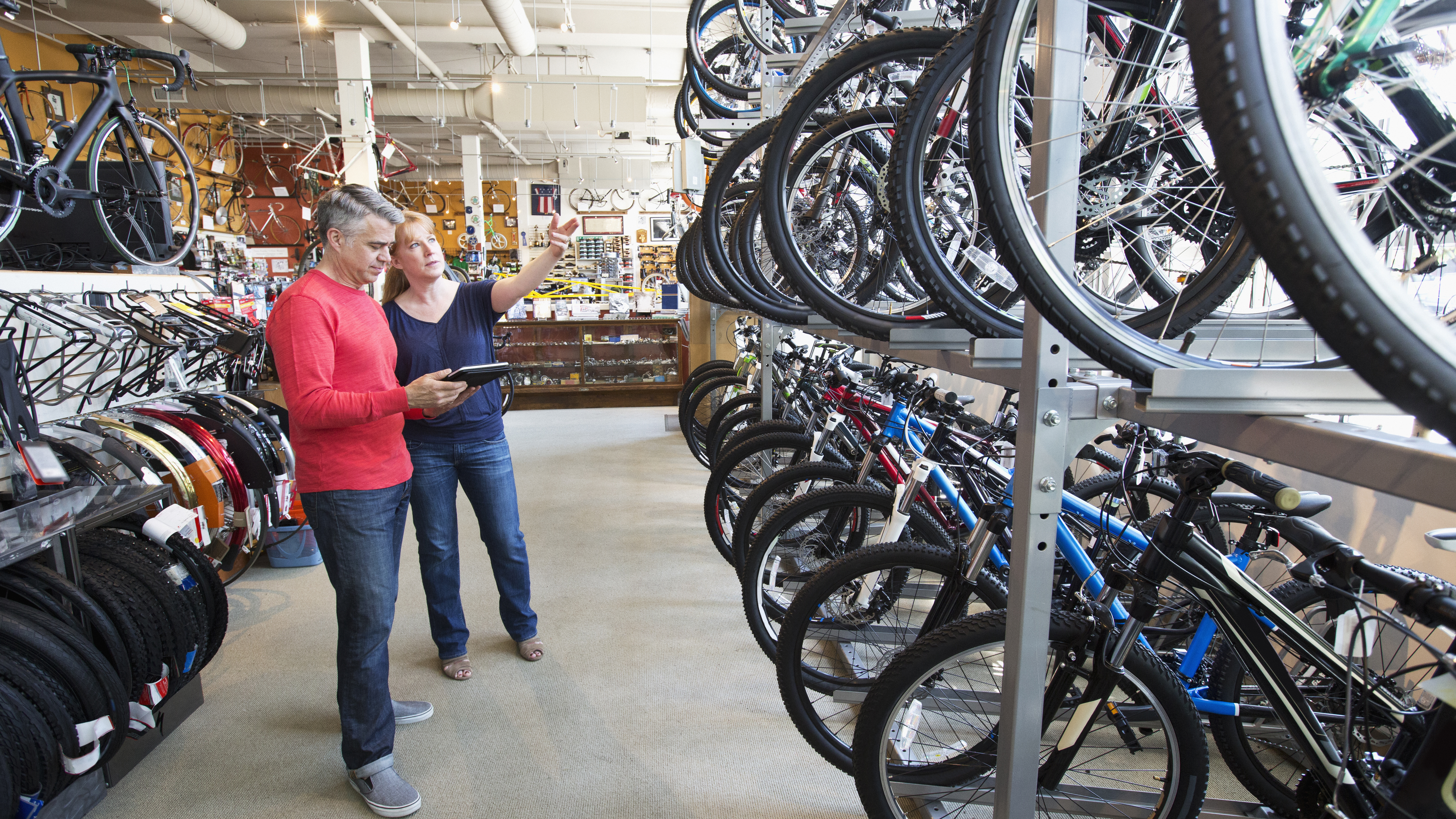 Salesman showing bicycles to customer in bicycle shop