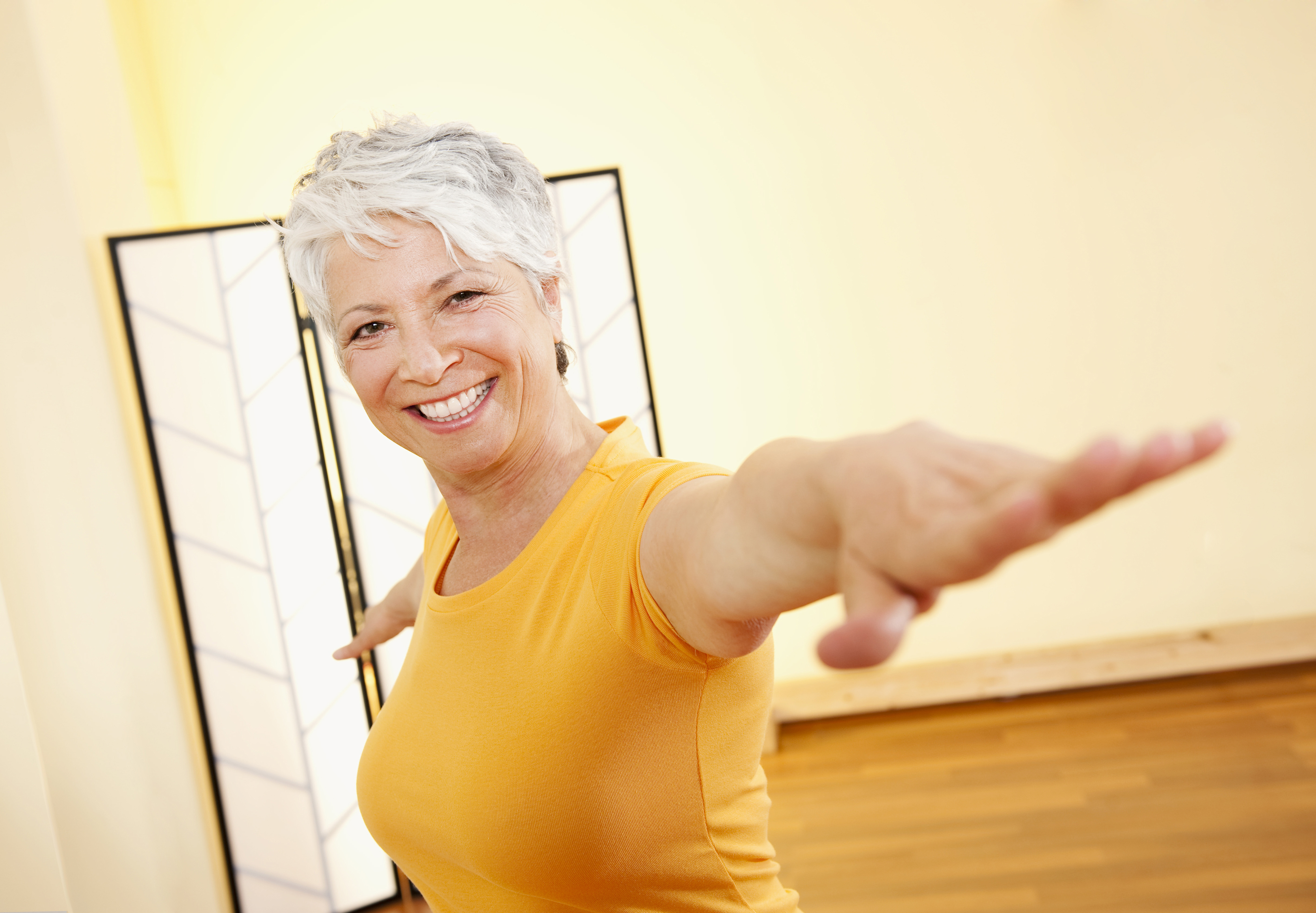 Senior woman with outstretched arms, smiling, portrait