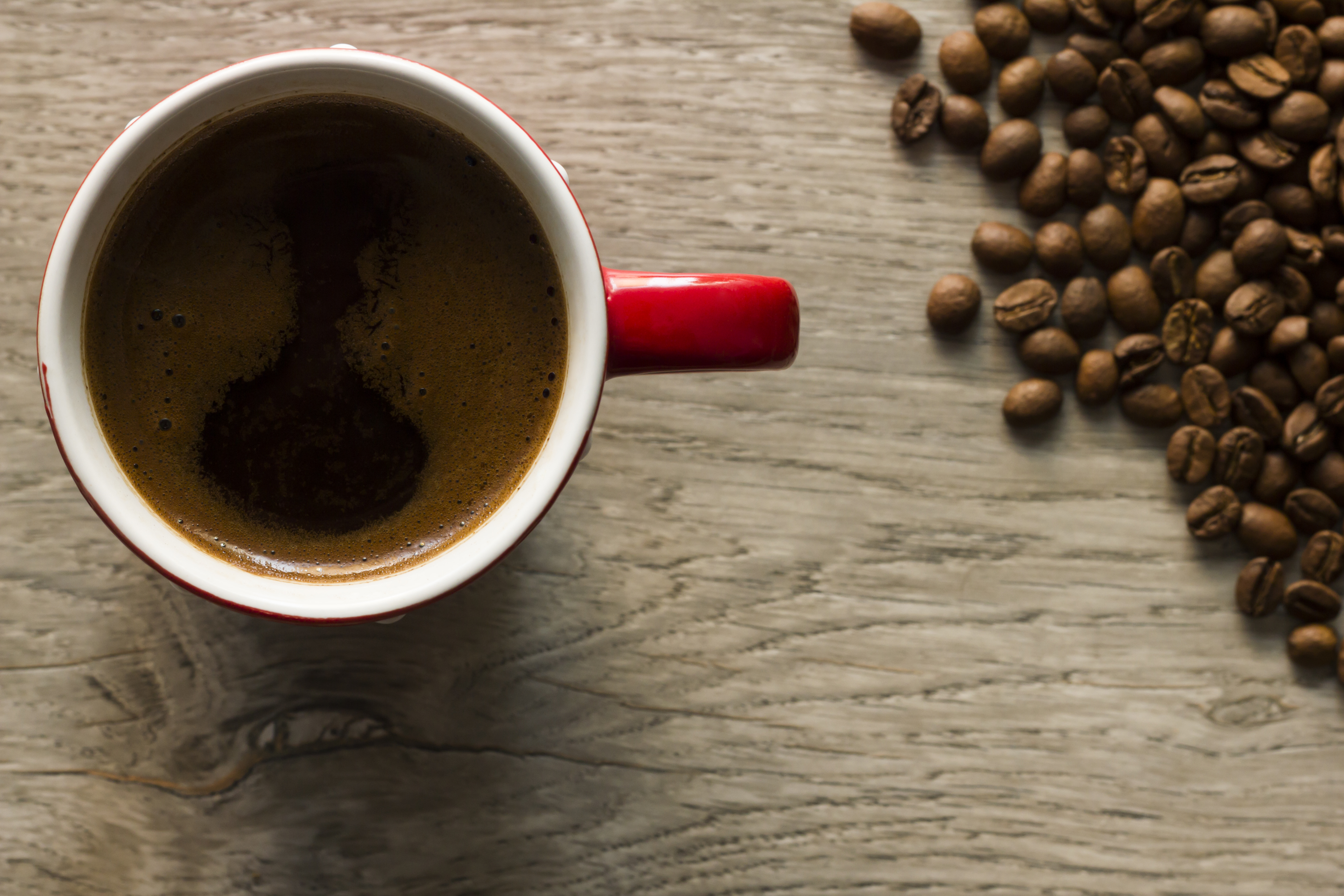 Cup of coffee and coffee beans viewed from directly above