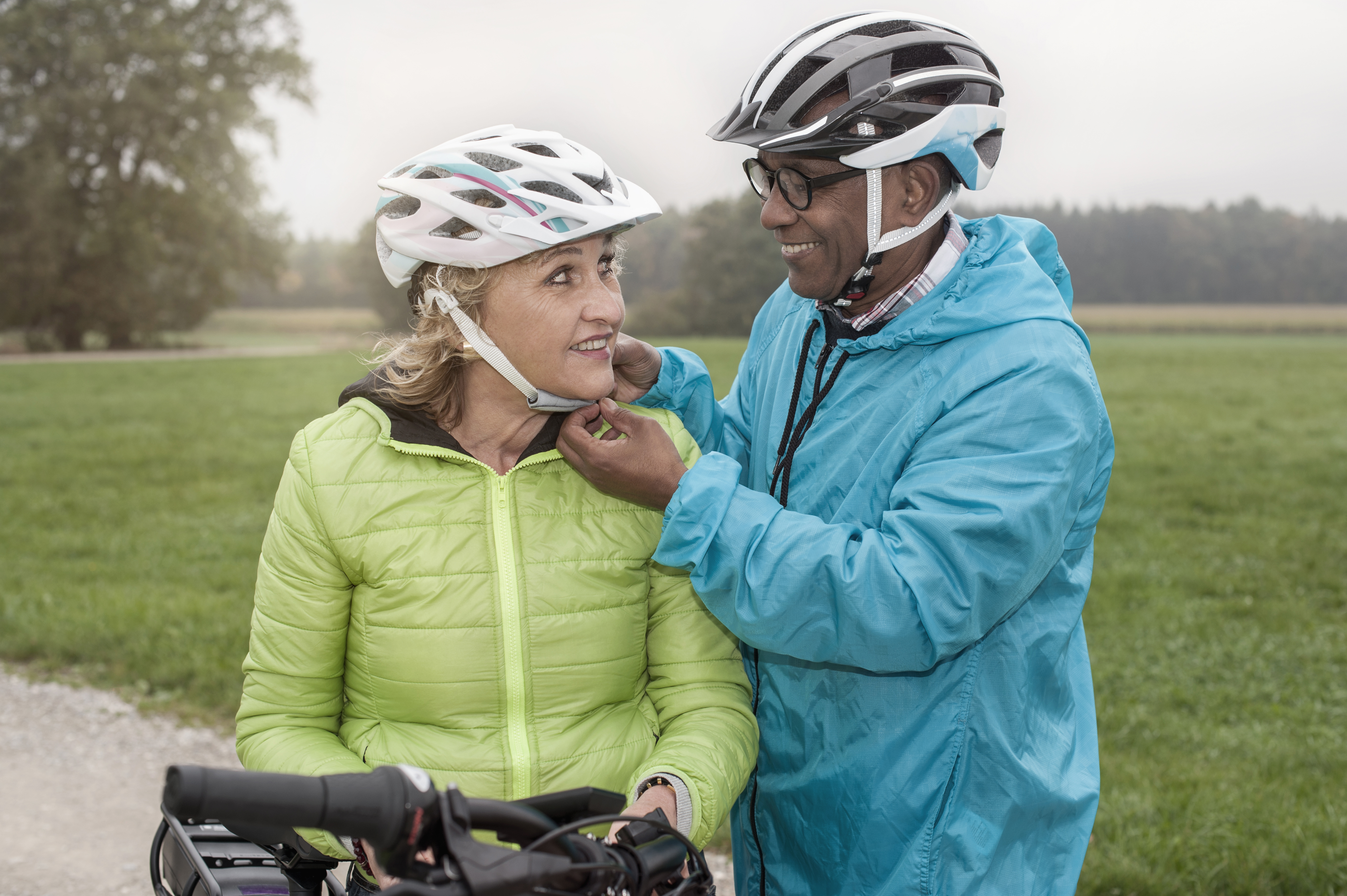 """Senior man fastening on bicycle helmet to his wife and smiling, Bavaria, Germany"""