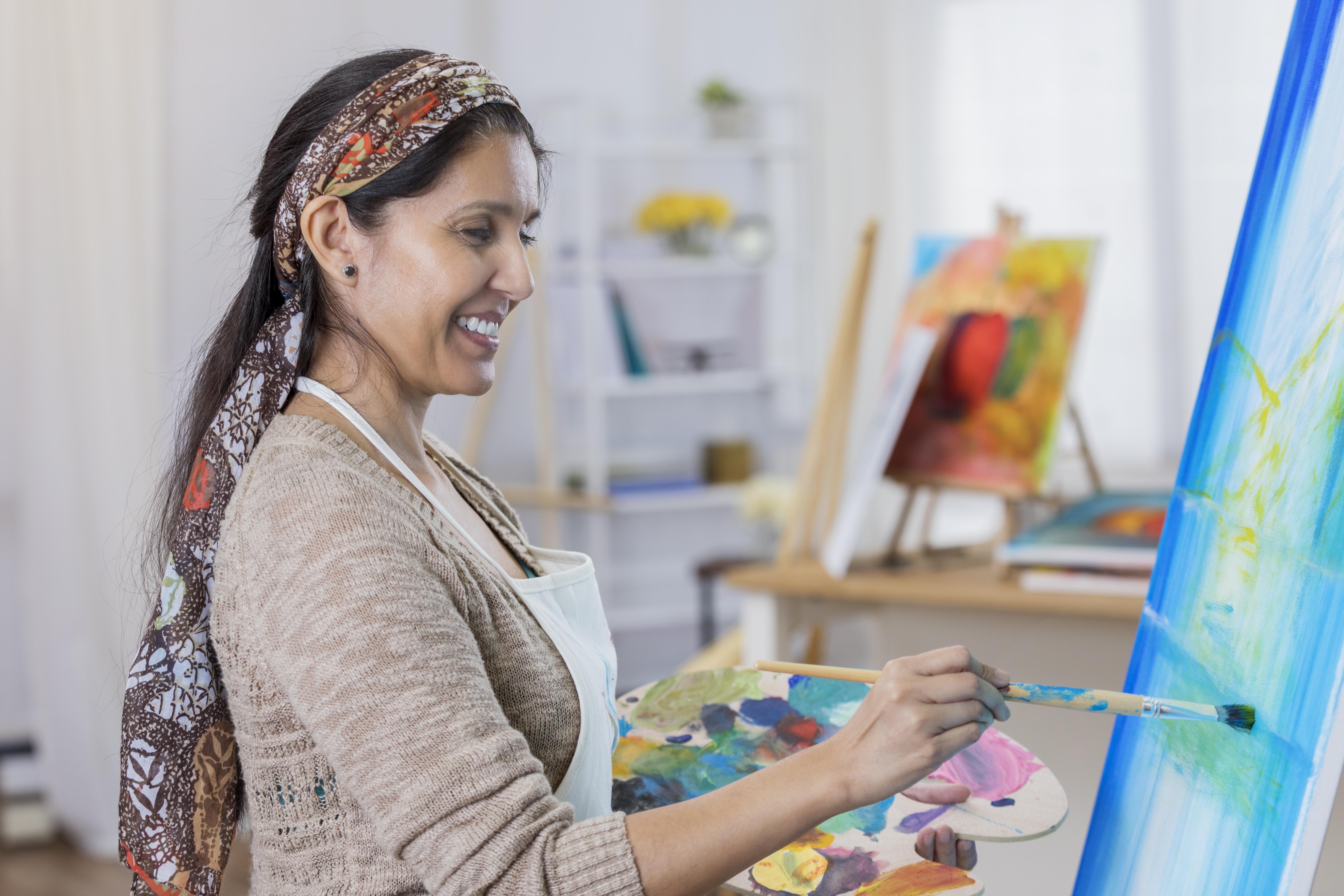 Beautiful woman paints in her art studio