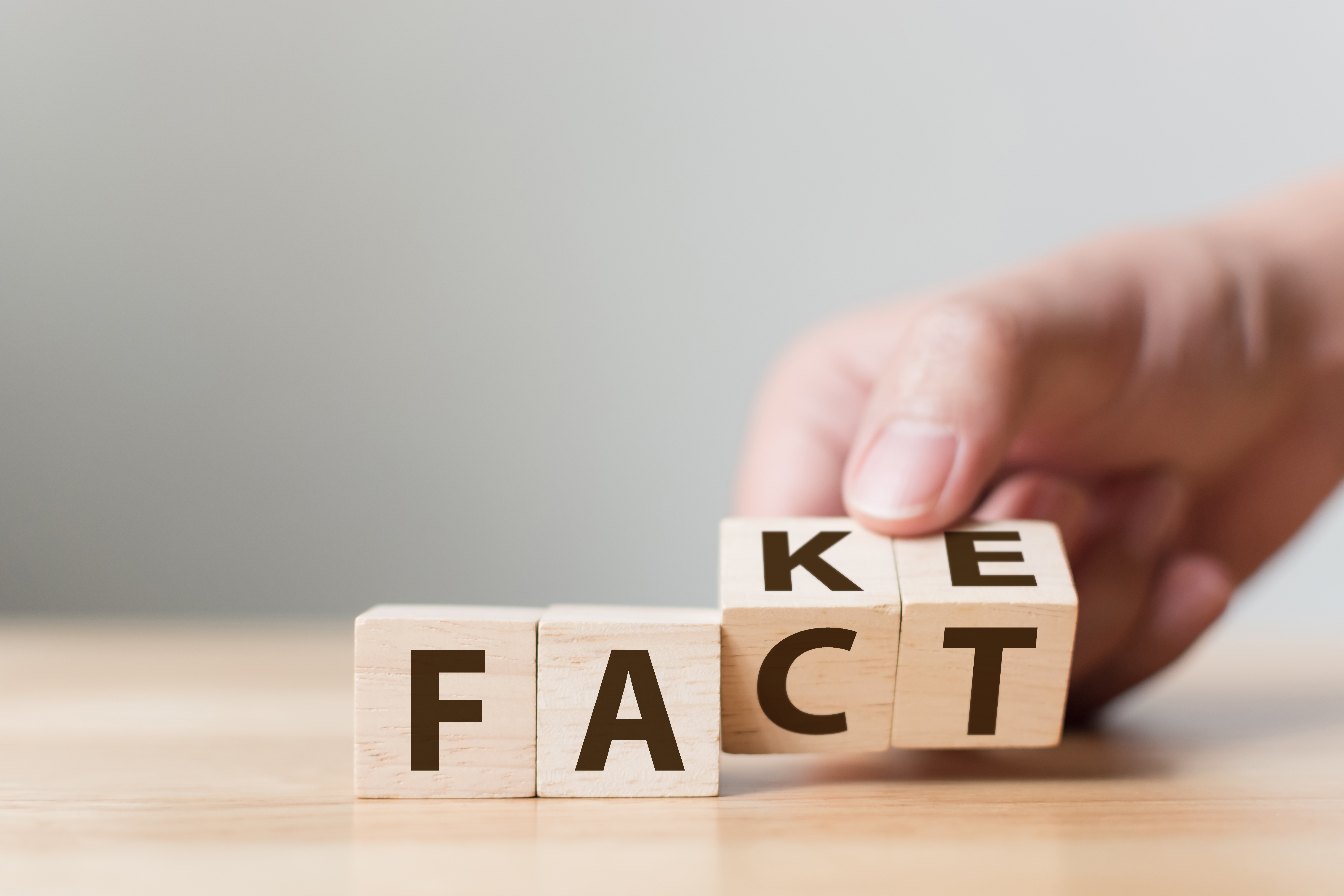 Fact or Fake concept, Hand flip wood cube change the word, April fools day