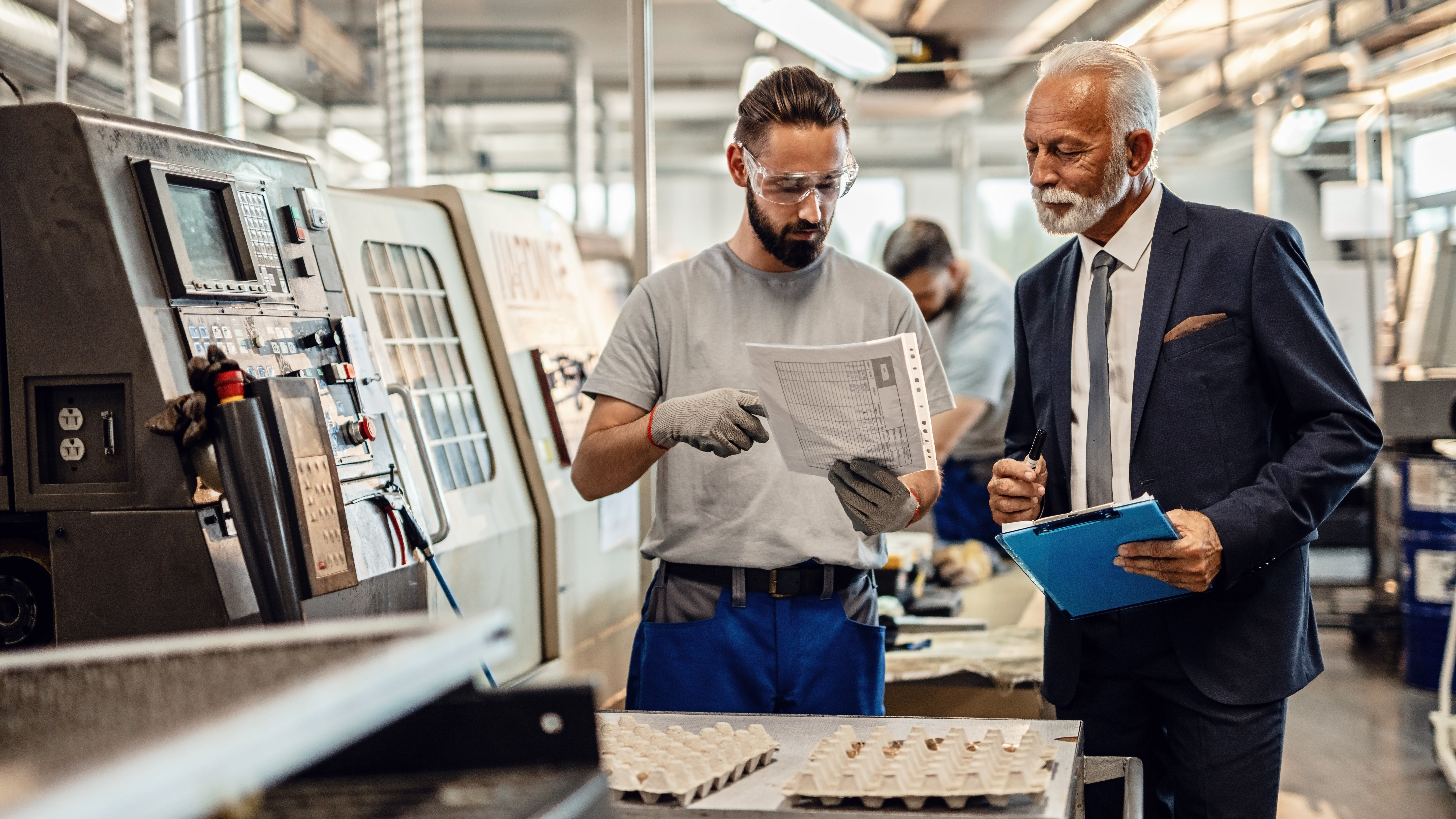 Mature company manager and worker going through reports in industrial facility.