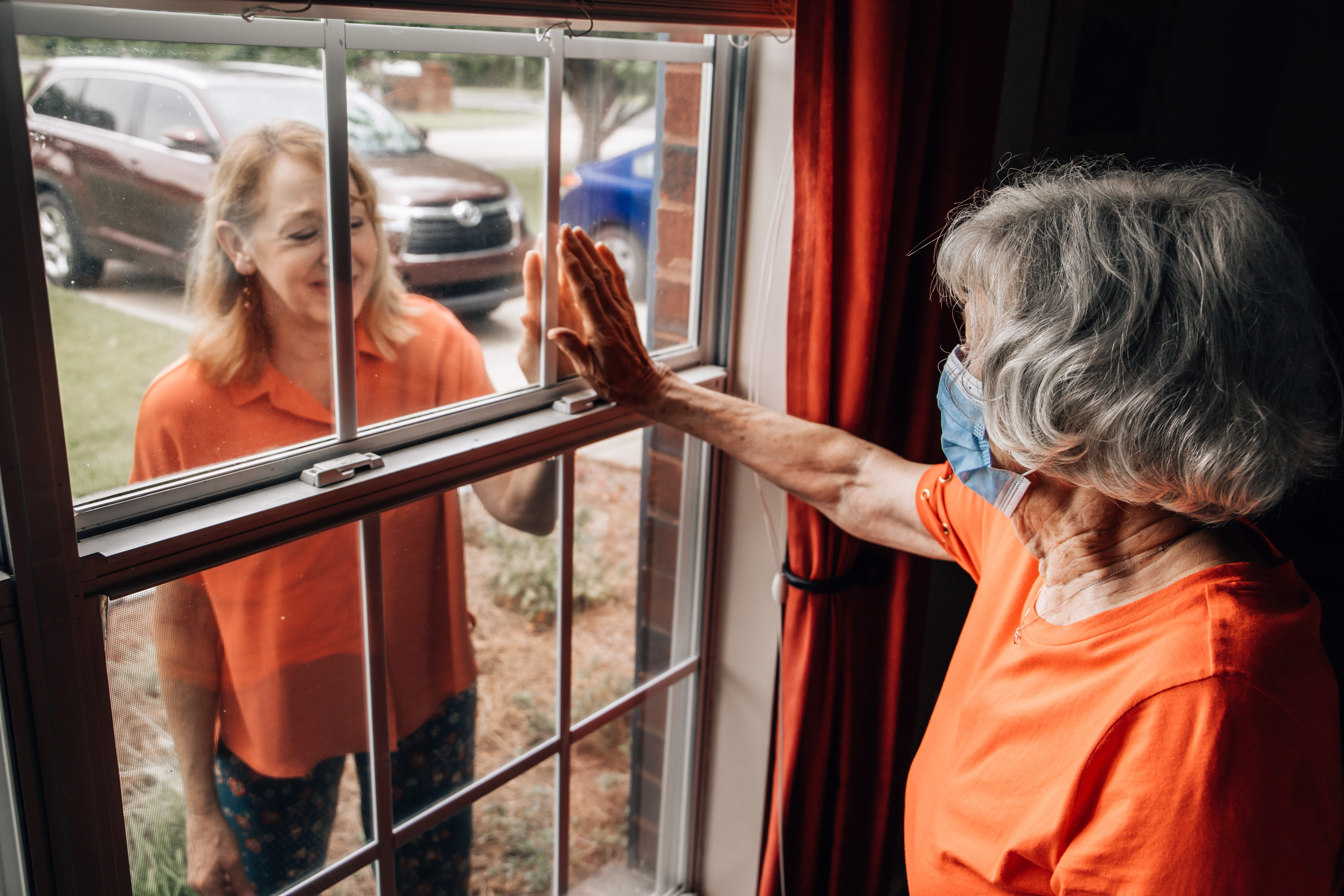A baby boomer daughter visiting her elderly shut-in mother in her 80's during quarantine from COVID-19 coronavirus through a window as to not catch this contagious disease