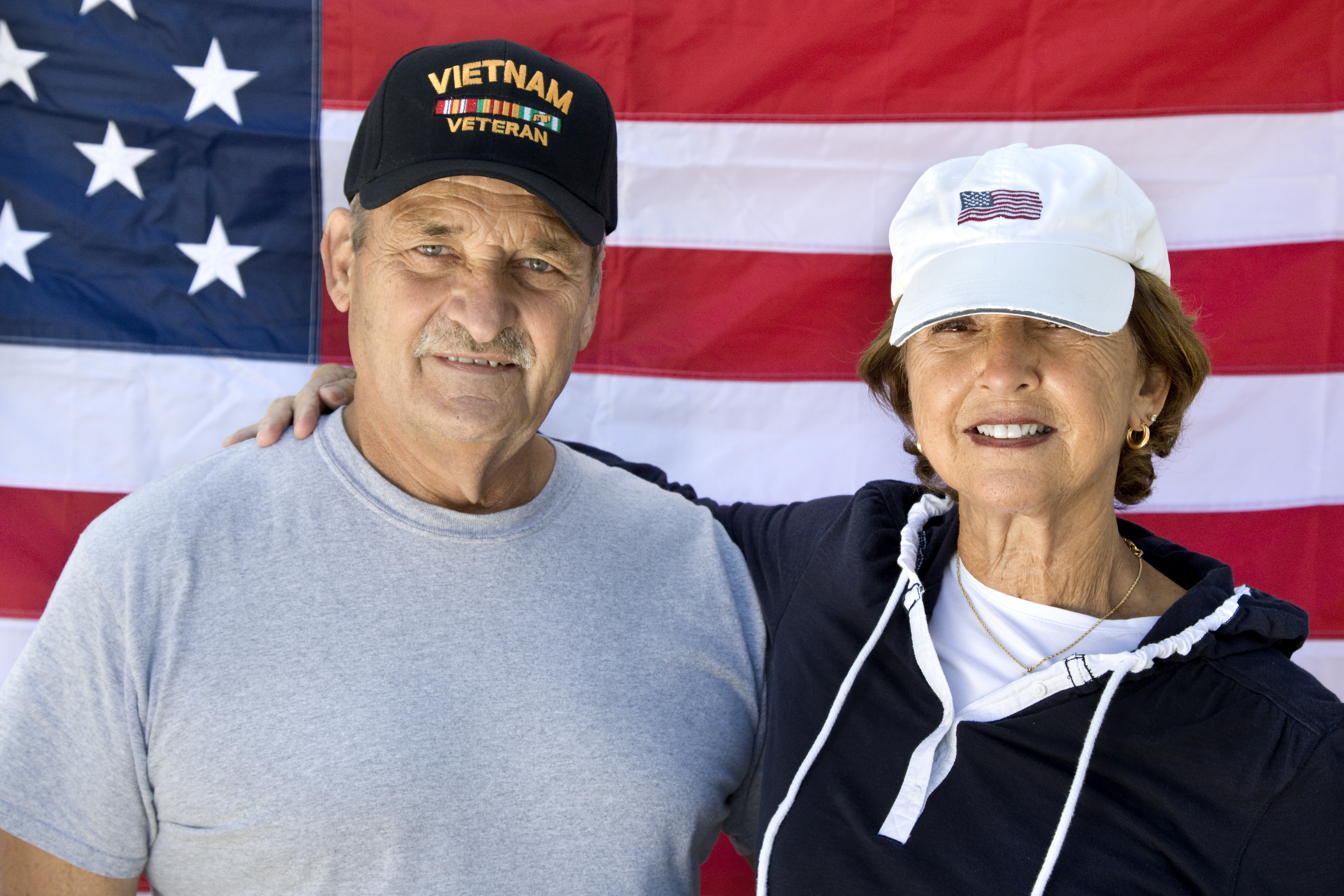 Vietnam Veteran and Wife looking at camera with American Flag in background