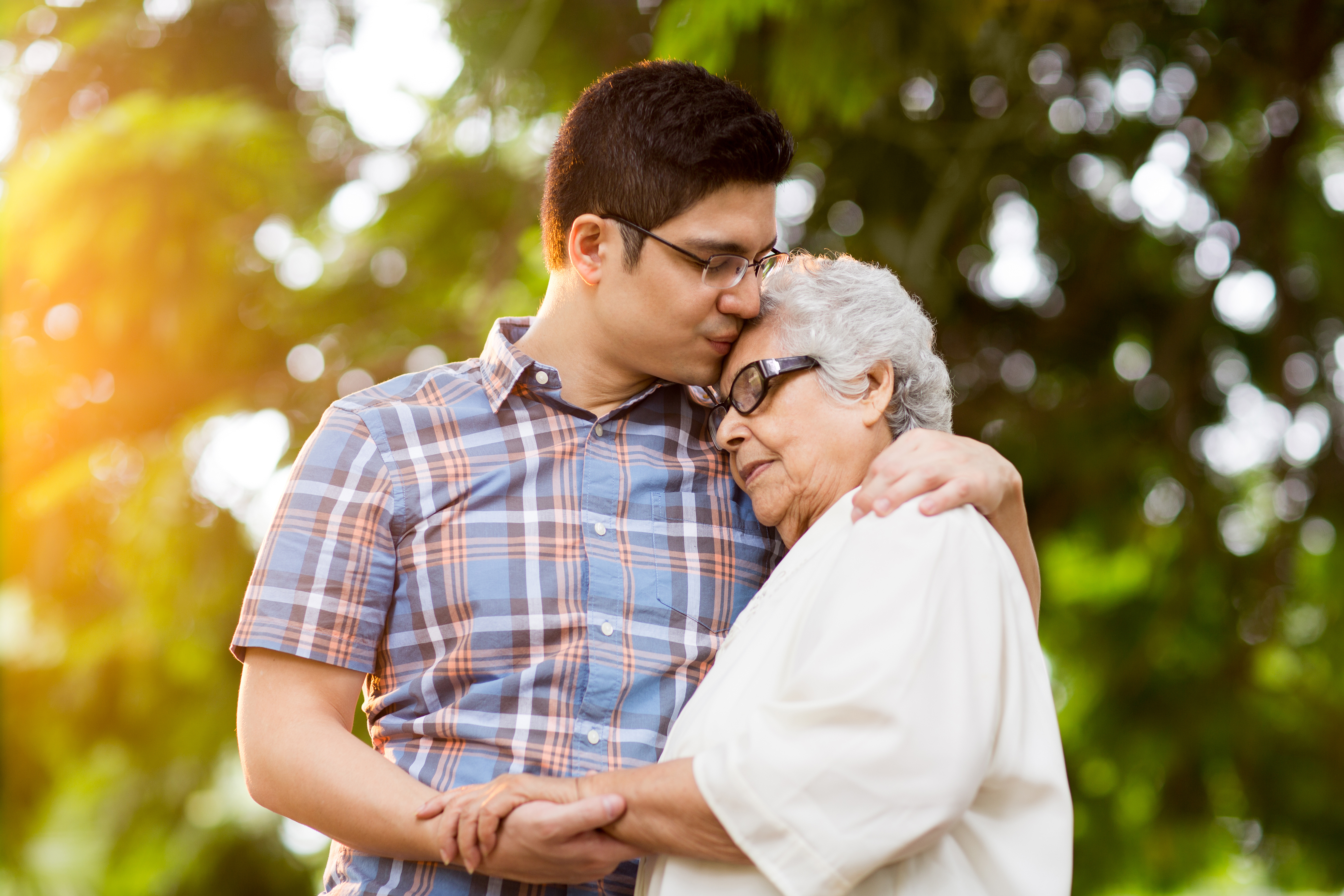 Latin grandson and grandmother embracing with eyes closed