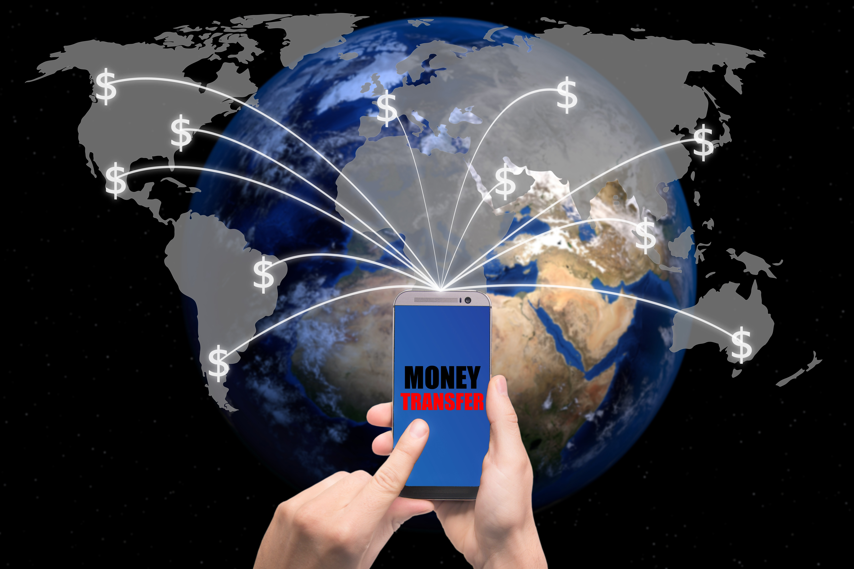 Hand holding smart phone sent money dollar bills flying away from screen to global map. Technology online banking money transfer, e-commerce concept.