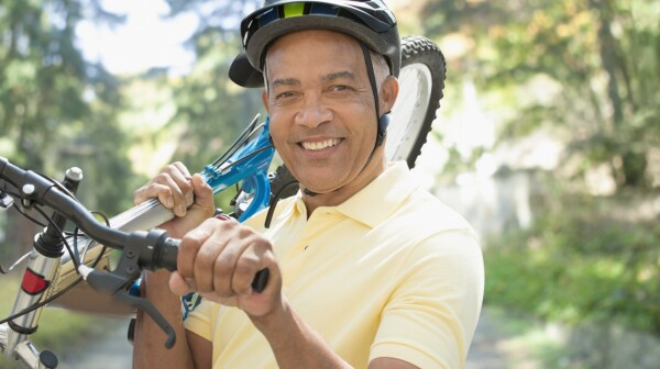 African American man carrying bicycle outdoors