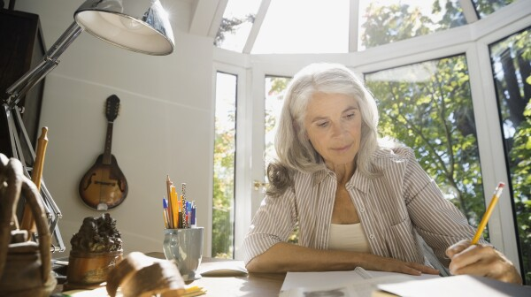 Senior woman writing in home office