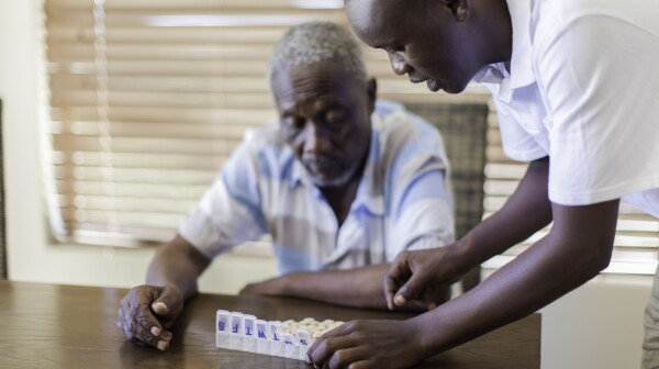 African grandson giving his grandfather medication.