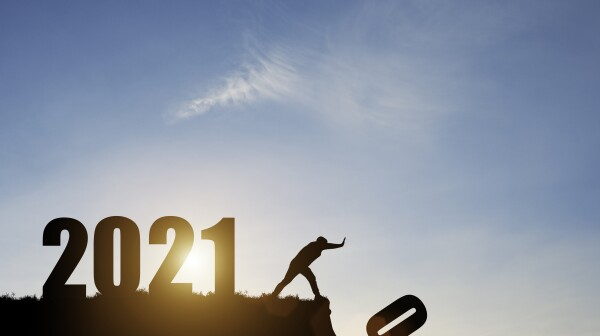 Man push number zero down the cliff where has the number 2021 with blue sky and sunrise. It is symbol of starting and welcome happy new year 2021.