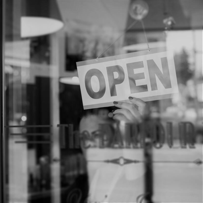 Hairdresser turning open sign in retro barbershop window