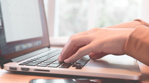Closeup woman's hands using on a laptop on a wooden desk