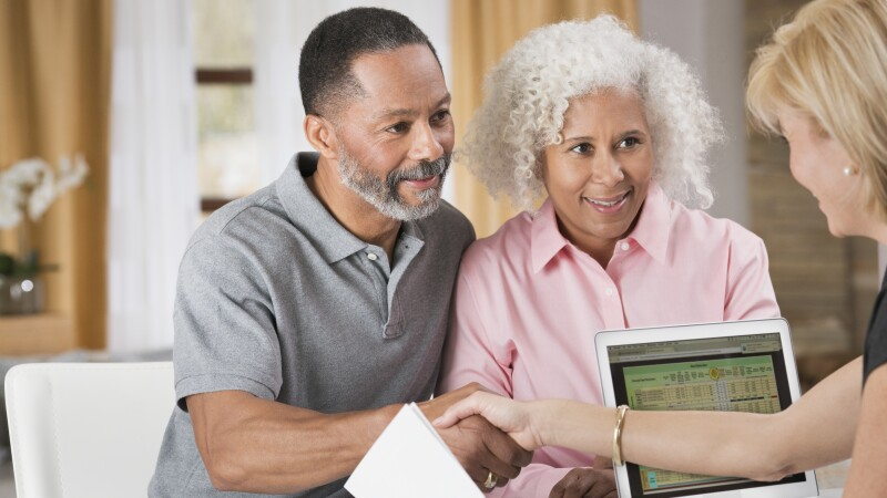 Older couple shaking hands with financial planner