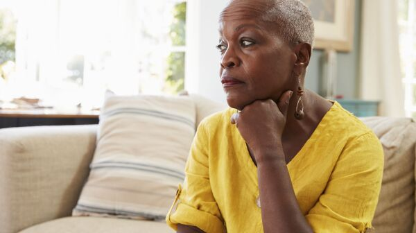 Senior Woman Sitting On Sofa At Home Suffering From Depression_large.jpg