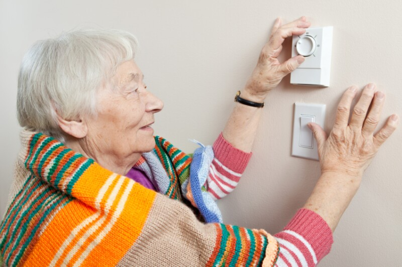 Elderly woman adjusting thermostat for heat