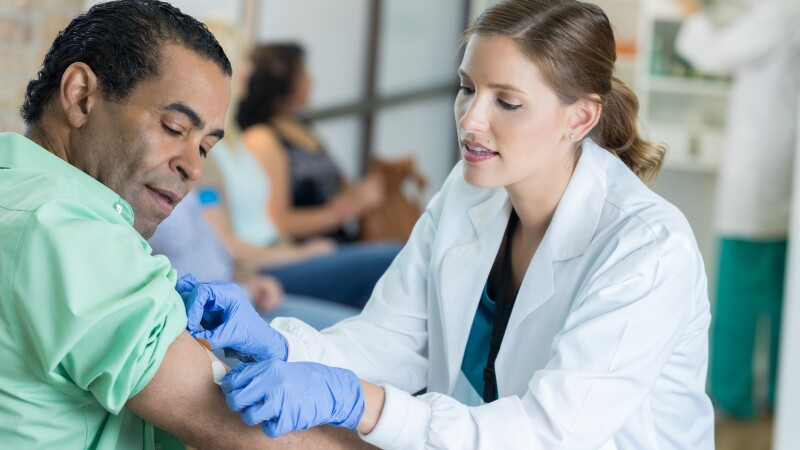Caring healthcare professional places bandage on man's arm