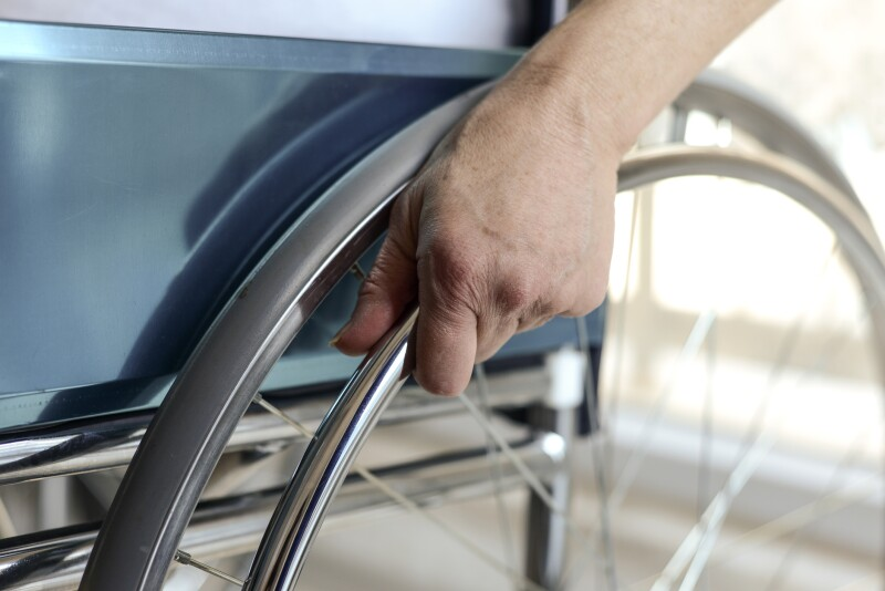 Senior Woman's Hand On Wheelchair