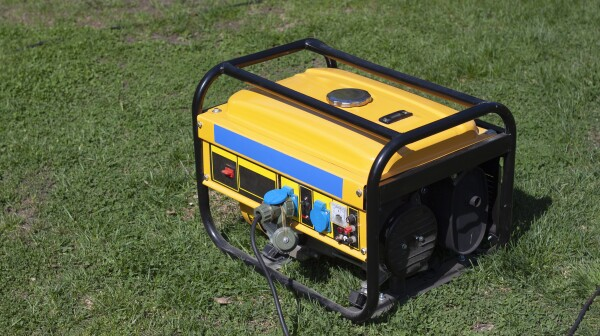 Powerful portable gas or diesel generator to provide electricity. Standing on the grass