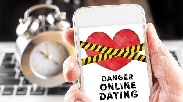 Hand holding mobile with caution tape on heart and Danger