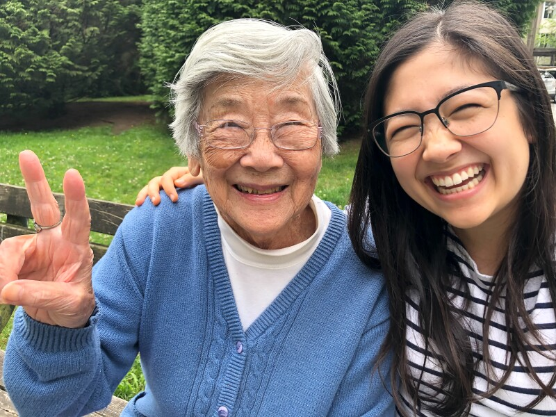 Asian Grandmother and Eurasian Granddaughter Smiling for Photo on Bench