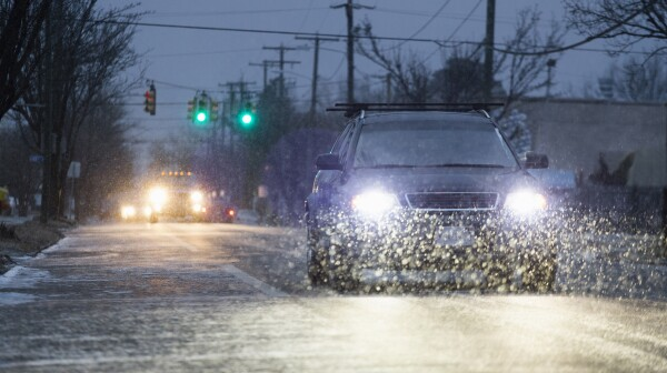 Car driving on snowy urban street at night