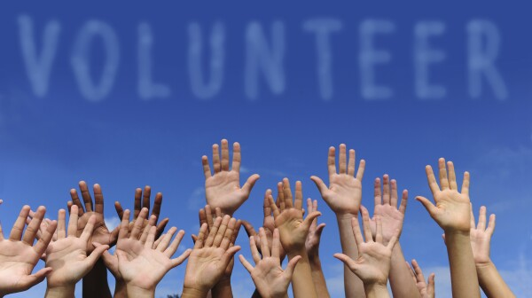 A group of raised hands below the word volunteer
