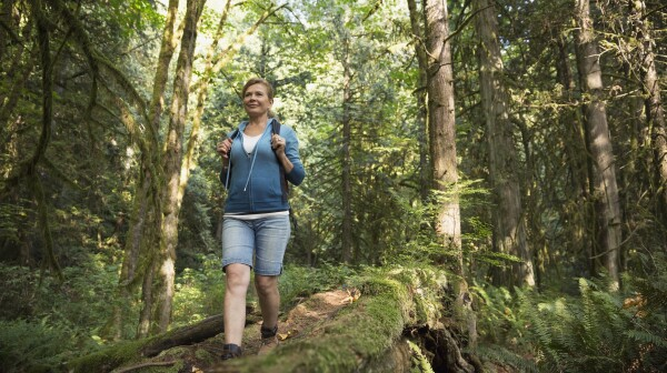 Woman descending hiking trail in woods