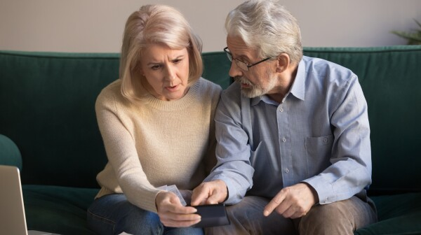 Serious stressed old couple looking at calculator feeling worried