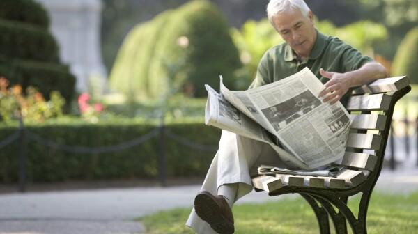 Senior man reading newspaper on park bench, Boston, Massachusetts