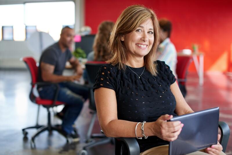 Confident female designer working on a digital tablet in red