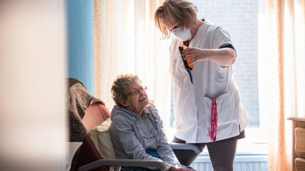 A nursing home aide holds a phone to assist a nursing home resid
