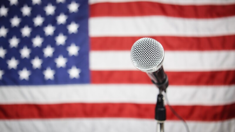 A microphone with an American flag in the background