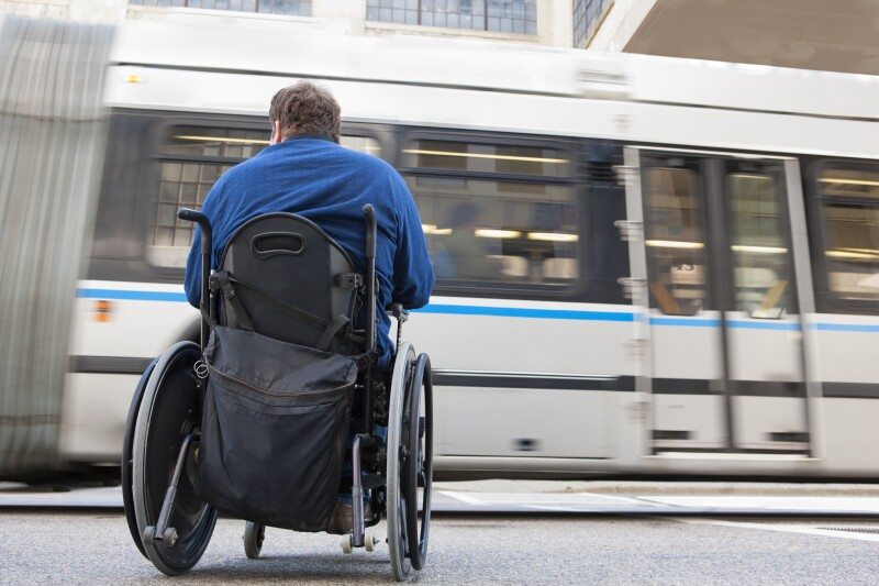 Man in wheelchair with spinal cord injury trying to catch a local bus