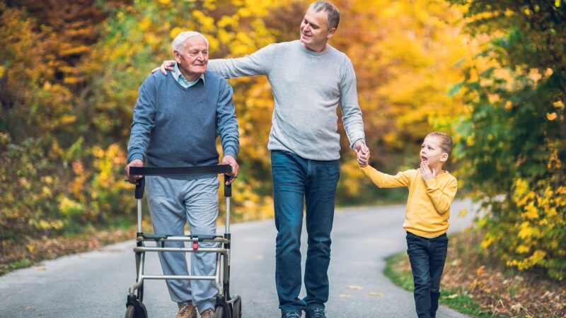 Elderly father adult son and grandson out for a walk in the park