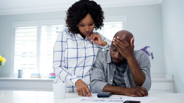 Worried couple interacting while checking the bills