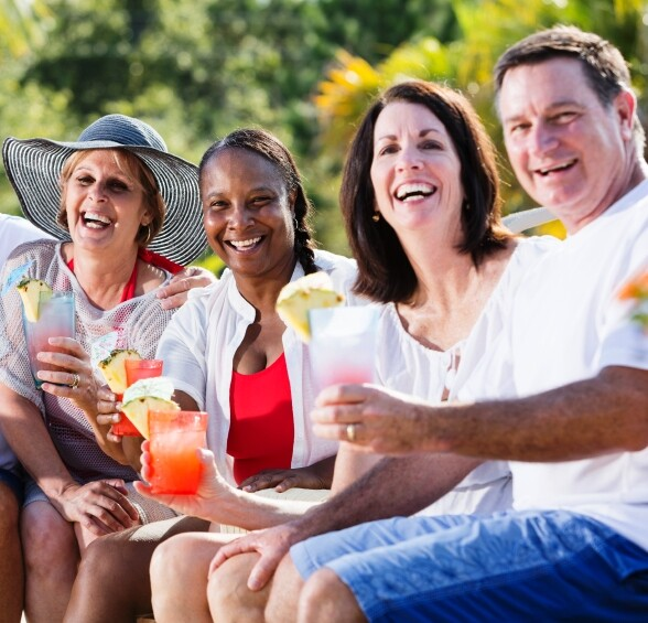 Multi-ethnic mature adults (50s, 60s) enjoying tropical drinks.  Main focus on African American woman in middle.